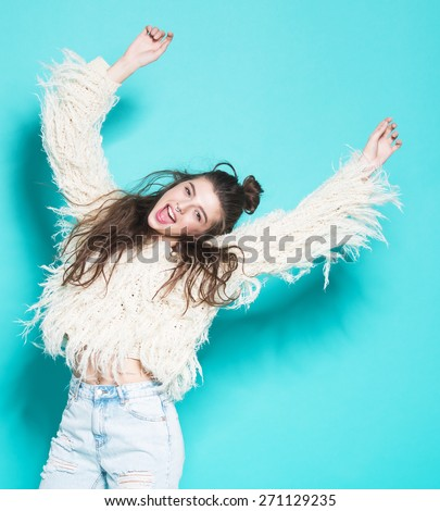 studio portrait of cheerful fashion hipster girl going crazy making funny face and dancing. Blue color background.