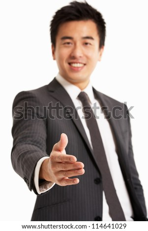 Studio Portrait Of Chinese Businessman Reaching Out To Shake Hands - stock photo