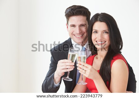 Studio Portrait Of Couple Celebrating With Champagne - stock photo