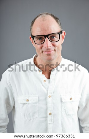 Studio portrait of expressive middle aged man wearing white shirt and retro glasses isolated on grey background