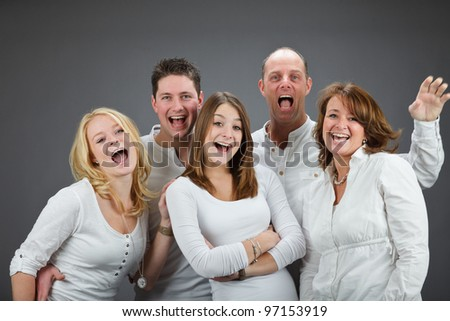 Studio portrait of family with white shirt isolated on grey background