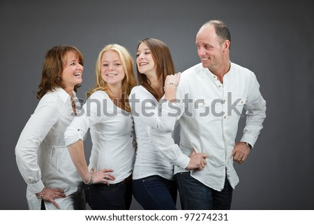 Studio portrait of family with white shirt isolated on grey background - stock photo