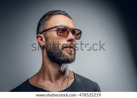 Studio portrait of fashionable male in sunglasses isolated on grey background.