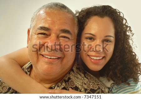 Studio portrait of father and daughter laughing and being happy