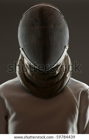 Studio portrait of fencing athlete wearing face protective mask - stock photo