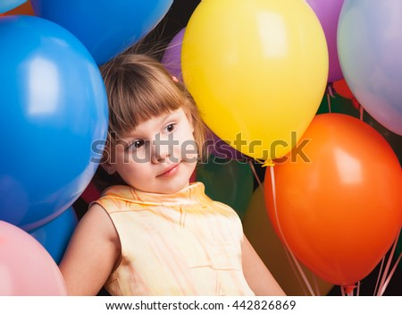 Studio portrait of funny little Caucasian blond girl with colorful balloons over back background - stock photo