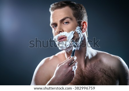 Studio portrait of handsome young man. Man with naked torso and shaving foam on face looking at camera and shaving - stock photo