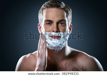 Studio portrait of handsome young man. Man with naked torso looking at camera and covering face with shaving foam - stock photo