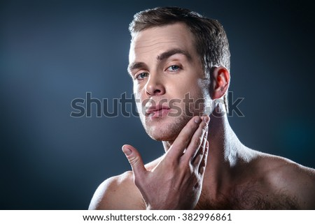 Studio portrait of handsome young man. Man with naked torso using cream after shaving - stock photo