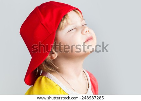 Studio portrait of happy baby girl with closed eyes in red baseball cap over gray wall background - stock photo