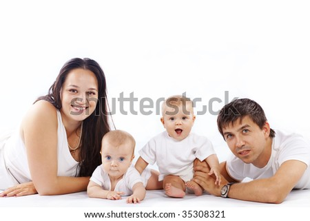 Studio portrait of happy young family with little children - stock photo