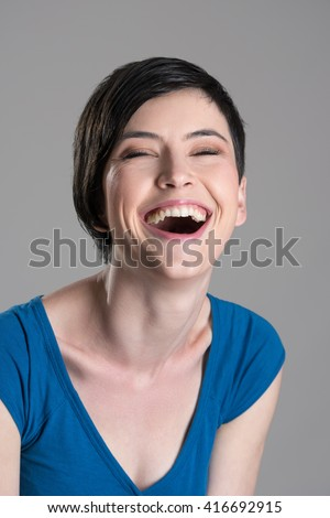 Studio portrait of heartily laughing young cheerful woman with open mouth over gray background