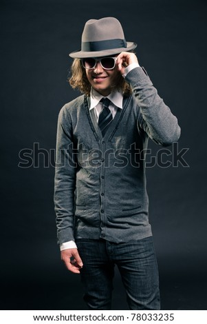 Studio portrait of hip cool looking young man with hat and white sunglasses on black background.