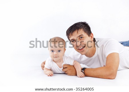 Studio portrait of loving young father hugging his child - stock photo
