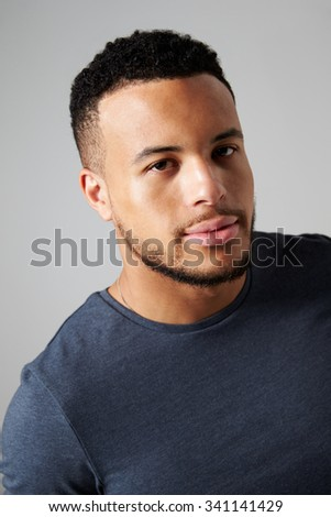 Studio Portrait Of Man Standing Against Grey Background - stock photo