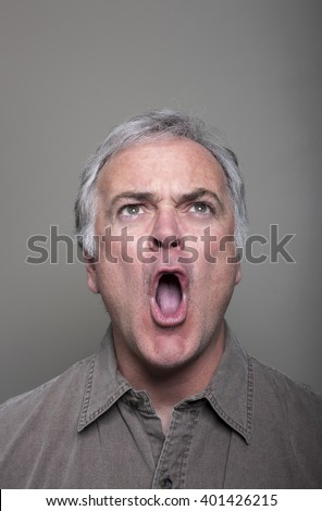 Studio portrait of mature man screaming with anger.