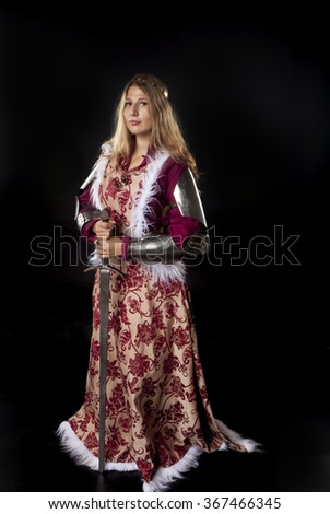 Studio portrait of medieval girl with golden hair and royal posture leaning on a sword - stock photo