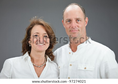 Studio portrait of middle aged couple wearing white shirt isolated on grey background - stock photo