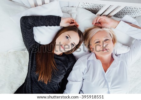 Studio portrait of mother and adult daughter. Lying on the bed, looking at the camera. Closeup - stock photo