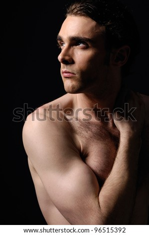 Studio portrait of muscular young man against black background - stock photo