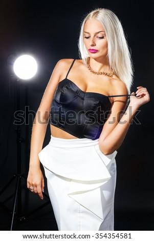 studio portrait of pretty fashionable girl on black - stock photo