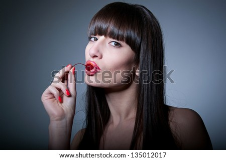Studio portrait of pretty woman model with natural makeup, long healthy shiny hair and fringe, licking ripe fresh red cherry and looking at camera. Gray background