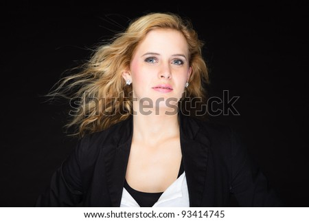 Studio portrait of pretty young woman with pink lipstick and long blond hair. Wearing a black suit. Isolated on black background.