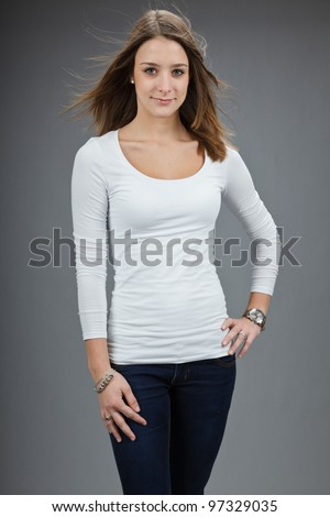 Studio portrait of pretty young woman with white shirt isolated on grey background - stock photo