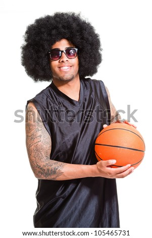 Studio portrait of retro basketball player with afro hair standing and holding ball isolated on white. Tattoos on his arms. Oldschool. - stock photo