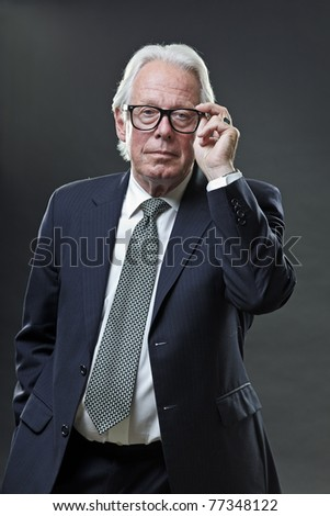 Studio portrait of senior business man holding his glasses with one hand. - stock photo
