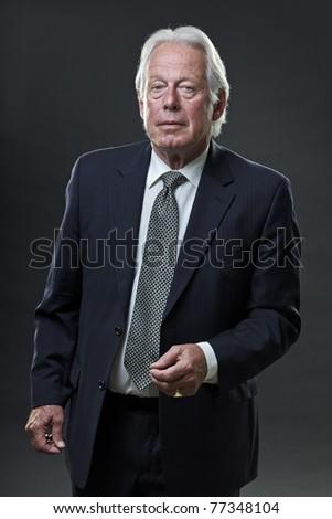 Studio portrait of senior business man looking serious. - stock photo