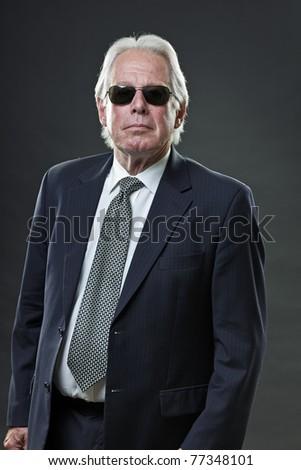 Studio portrait of senior business man with black sunglasses looking tough. - stock photo