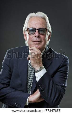 Studio portrait of senior business man with sunglasses looking confident. - stock photo