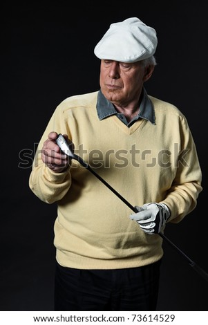 Studio portrait of senior golf man holding golf stick with yellow shirt and white cap. Black background. Club. - stock photo