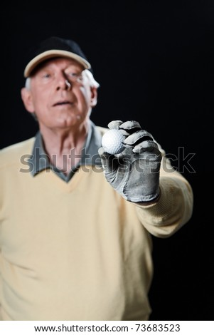 Studio portrait of senior golf man with yellow shirt and black cap holding golf ball. Black background. - stock photo