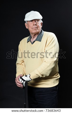 Studio portrait of senior golf man with yellow shirt and white cap holding golf club. Black background. Concentration. Resting. Serious. - stock photo