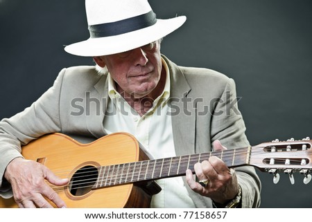Studio portrait of senior man with hat playing acoustic guitar. Jazz musician. - stock photo