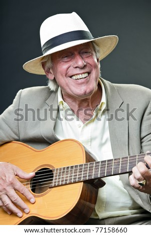 Studio portrait of senior man with hat playing acoustic guitar. Jazz musician.