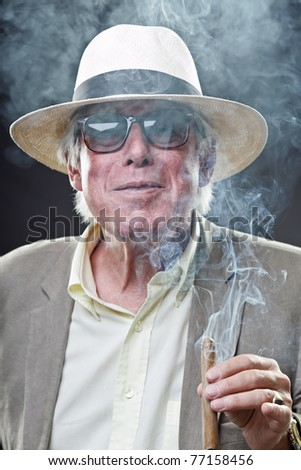 Studio portrait of senior man with hat sunglasses and cigar. Gangster look. - stock photo