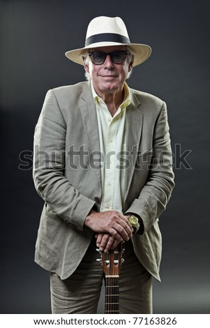 Studio portrait of senior man with hat sunglasses and guitar. Jazz musician.