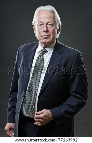Studio portrait of serious senior business man in blue suit. - stock photo