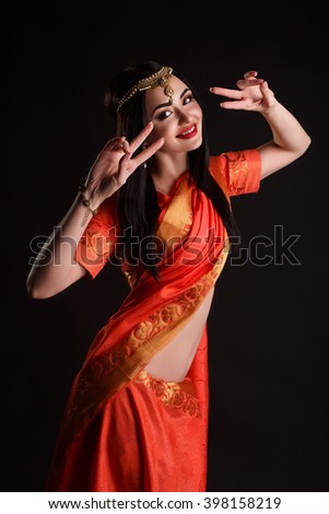 studio portrait of sexy girl in traditional Indian clothing and jeweleries. Beautiful Indian girl in traditional Indian sari. Young girl dressed in purple silk sari with jewels. - stock photo