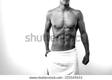 Studio portrait of sexy sporty young man. Muscular man with naked torso and towel on hips. Black and white photo - stock photo