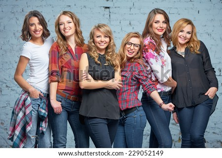 Studio portrait of Six young happy attractive smiling caucasian women dressed in jeans grouped together - stock photo