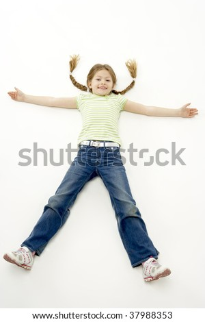 Studio Portrait of Smiling Girl lying down with arms and legs spread - stock photo