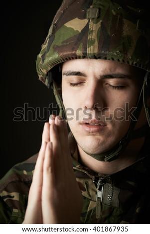 Studio Portrait Of Soldier In Uniform Praying - stock photo
