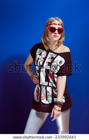 Studio portrait of teenage hipster or hippie girl wearing trendy flower wreath over blue copy space background