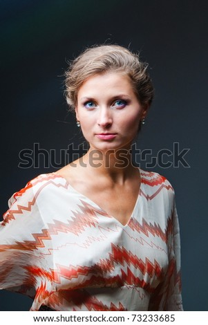 Studio portrait of the girl against a dark background - stock photo