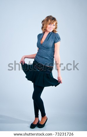 Studio portrait of the posing girl on a gray background - stock photo