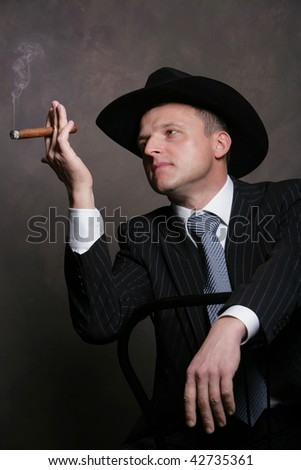 Studio portrait of the young attractive man in a black hat with a cigar